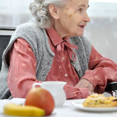 older woman sitting at a table with food