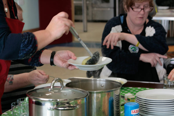 serving up soup bowls to group cookery
