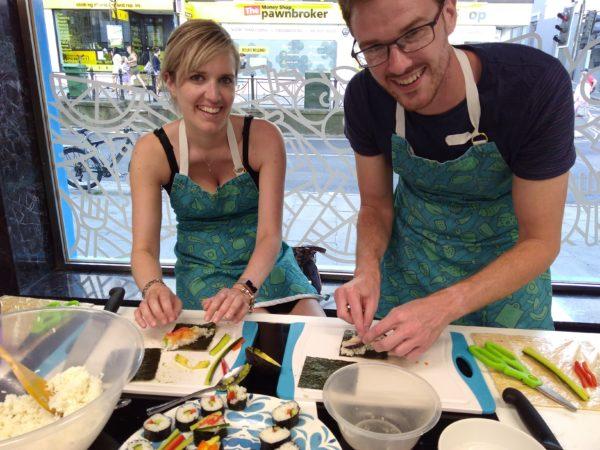 smiling couple rolling sushi