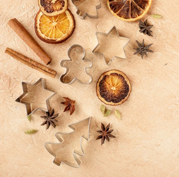 Dried orange slices, cinnamon sticks, anise stars, cardamom seeds and metal cutters for Christmas cookies on a light background