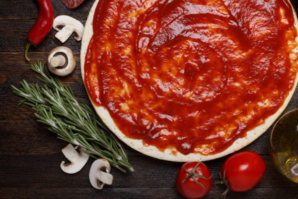 19717870 - fresh pizza dough with tomato sauce and natural ingredients for cooking on wooden table